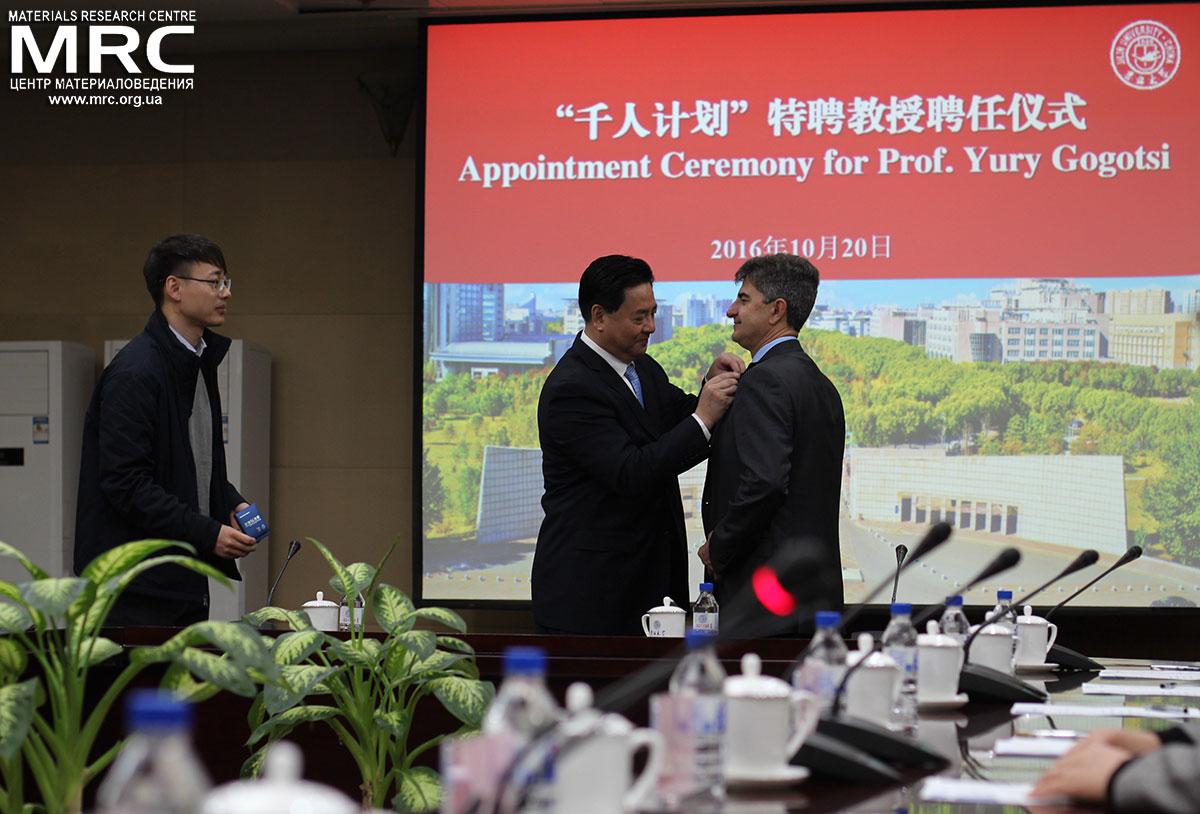 Ректор Цзилиньского Университета Ли Юаньюань вручает профессору Юрию Гогоци значок с эмблемой Цзилиньского Университета, Чанчунь, Китай, 20 октября 2016