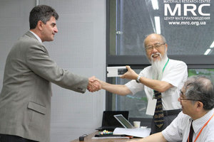 Prof. Gogotsi is giving a present to prof. Yoshimura